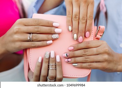 Close up of trendy leather pink bag with two girls hands with design manicure over it, showing at camera. Women hands with elegance silver rings. Concept of manicure, fashion and beauty salon.
