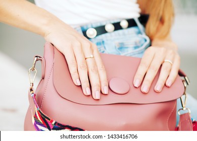 Close up of trendy leather pink bag with woman hands with pastel color manicure. Women hands with elegance golden rings. Concept of manicure, fashion and beauty salon.