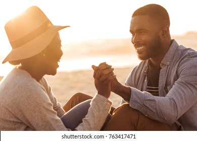 Close up of trendy young African couple sitting and holding hands together on a sandy beach while enjoying a romantic sunset
