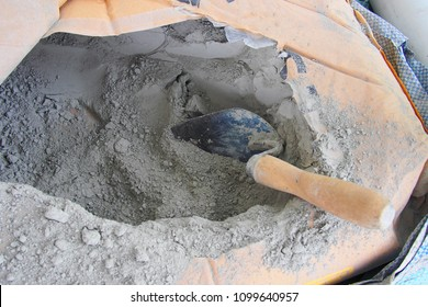close up trowel in a bag of cement powder