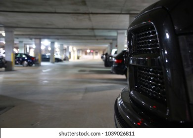 Close Up of Truck Grille in Front of Parking Garage Out of Focus in the Background