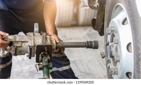 Close up of Truck Wheel mechanic hands using a pneumatic gun to loosen a wheel nut in a mechanical workshop  in the Truck Service Center.
