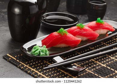 close up of tuna sashimi sushi set with chopsticks and soy on stone table  .Top view