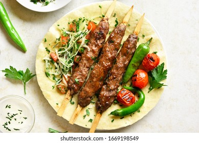 Close up of turkish Adana Kebab with fresh vegetables on flatbread over light stone background. Top view, flat lay