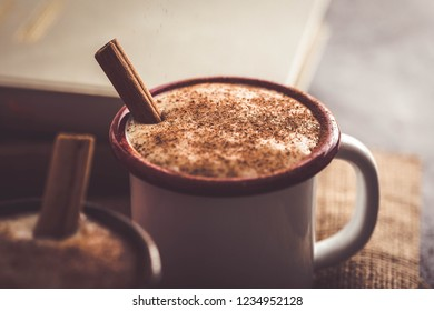 Close up Turkish salep (milky traditional hot drink) with cinnamon sticks on sack fabric