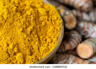 Close up of turmeric powder in bowl with roots in background