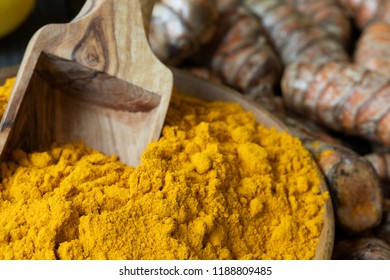 Close up of turmeric powder in bowl with scoop and turmeric roots in background.