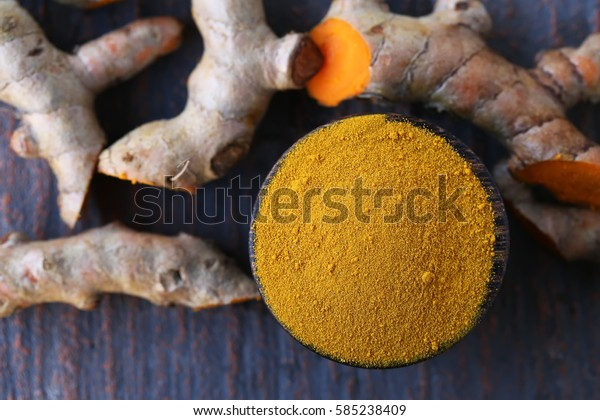 Close up turmeric powder and fresh turmeric on wooden background.