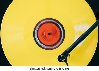 Close up of turntable tonearm play yellow color vinyl record