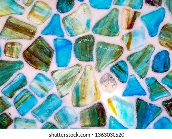 close up of turquoise and green agate stone in mosaic pattern on white background