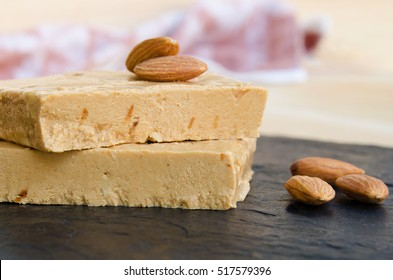 Close up of Turron, typical Christmas sweet in Spain. Almond nougat on black stone background.