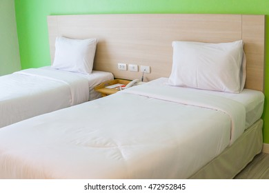 Close up twin beds with light brown wood headboard are neatly done in a hotel room. Suitable for concepts such as travel, tourism, vacation and holiday -  oblique angle shot