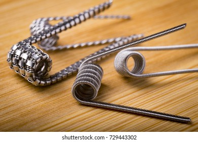 close up twisted coils for e cig or electronic cigarette for vape devices, RDA prebuild coil clapton over a wooden background.