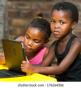 Close up of two African kids doing homework on tablet outdoors.