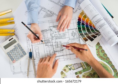 Close Up Of Two Architects Discussing Plan Together At Desk With Blueprints