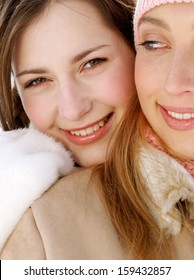 Close up of two attractive girls friends with their arms around each others shoulders, being joyful and smiling with their heads together while wearing warm coats and jackets in winter.