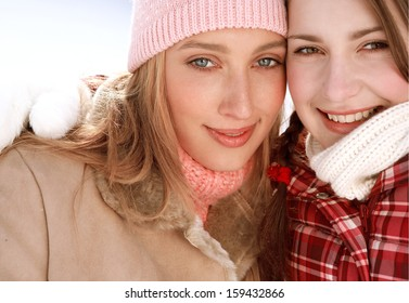 Close up of two attractive girls friends with their arms around each others shoulders, being joyful and smiling with their heads together while visiting the snow mountains in winter.
