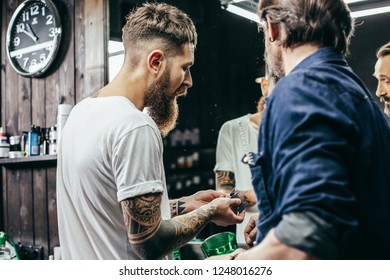 Close up of two bearded barbers standing close to each other and looking at new hair clipper blades