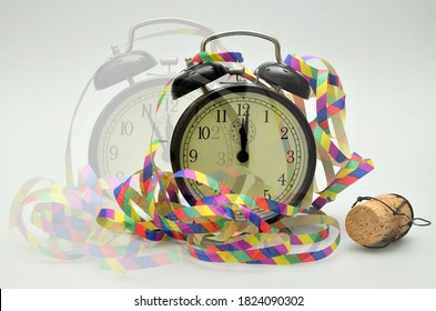 close up of  two black retro twin bell alarm clocks, around midnight, with paper streamers and cork of a bottle of sparkling wine