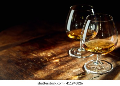 Close up of two bourbon filled glasses on wooden table in a dark room with a few rays of sunlight