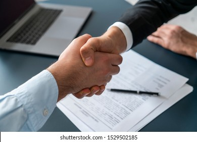 Close up of two businessmen shaking hands in blurred office with computer and contract on table. Concept of partnership and communication