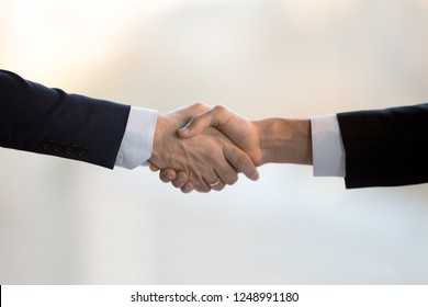 Close up two businessmen in suits shake hands greeting each other. Executive manager and client after successful negotiations handshaking. Boss congratulate new company employee is glad to cooperate