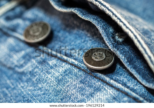 close up two buttons on blue jeans. Nice for a background.