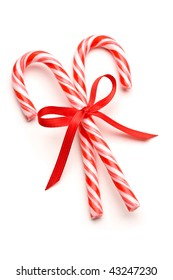 Close up of two candy canes tied with ribbon bow on white background