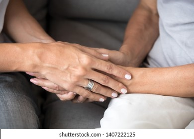 Close up two Caucasian female holding hands. Relative reliable person loving mother and daughter supporting each other. Symbol sign gesture of trusted friend, compassion empathy or forgiveness concept