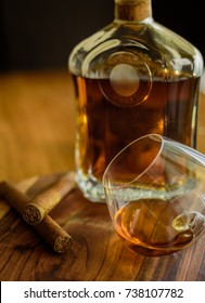 Close up of two cigars, a glass and a bottle of rum on a wooden surface