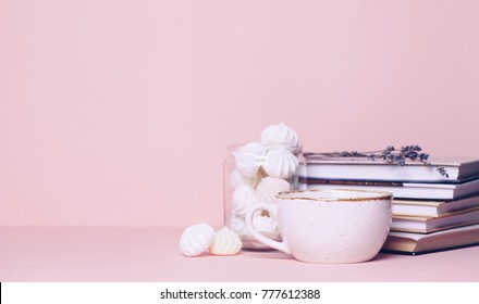 Close up of two cups and a book on pink background. Copy space for your text or design.