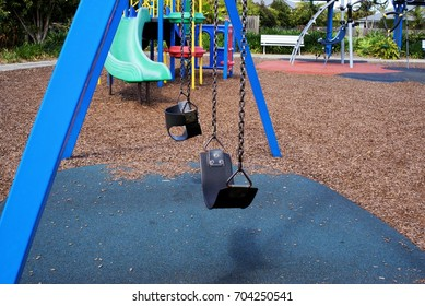 Close up of two empty swings in park attached with metal chain to metal posts. Fragments of wood and rubber laid as surface of the park.