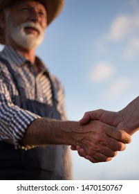 Close up of two farmers shaking hands in field against blue sky