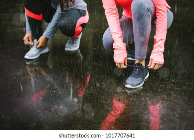 Close up of two female athletes lacing shoes and getting ready for urban running workout under the rain. Winter training and fitness lifestyle concept.