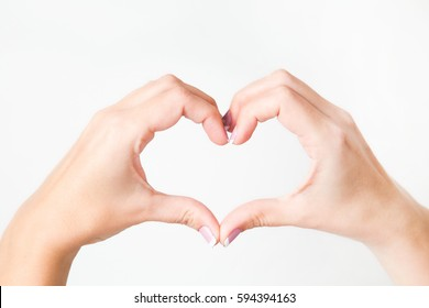Close up of two female caucasian hands isolated on white background. Young woman forming shape of heart with her fingers. Horizontal color photography. Point of view shot