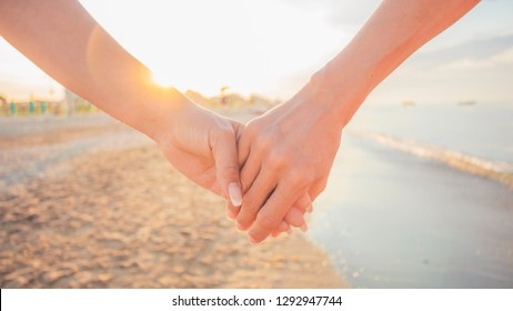 Close up of two female holding hands against sunset - two girls walking on the beach hand by hand - same-sex lesbian couple and female friendship and love, celebration of Valentine's Day concept.