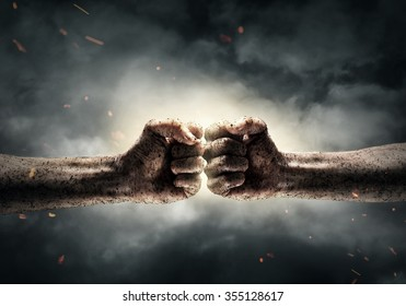 Close up of two fists hitting each other over dramatic sky background