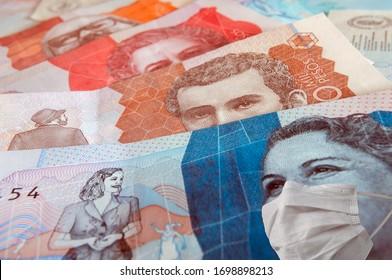 Cerca de dos cinco mil y veinte mil pesos colombianos con máscaras faciales que simbolizan el concepto de la crisis financiera en Colombia debido al coronavirus covid-19. Dinero colombiano