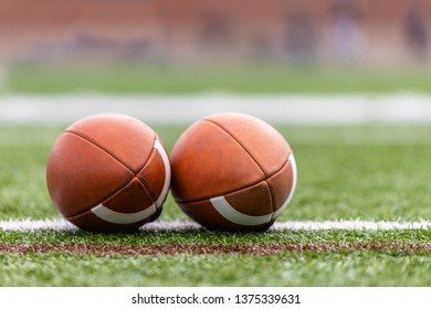 Close up of two football bals on the green field