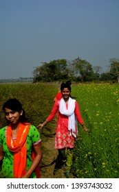 Close up of two girls walking in a rapseed/mustard field wearing salwar kameez, smiling, selective focusing