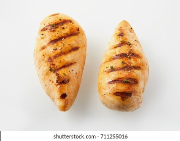 A close up of two golden, grilled chicken breasts with a white background and copy space.