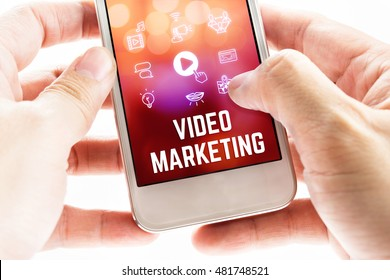 Close up Two hand holding mobile phone with Video marketing word and icons, Online Digital Marketing concept.