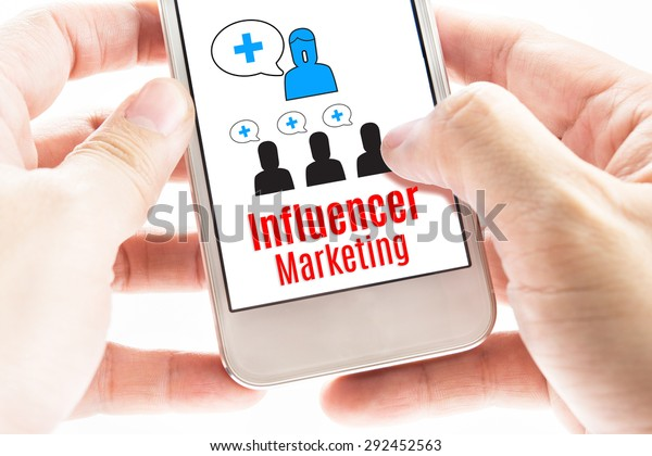 Close up Two hand holding smart phone with Influencer Marketing word and icons, Digital concept.