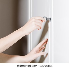 Close up of two hands opening the door with a key