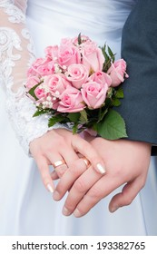 close up of two  hands with wedding rings holding wedding bouquet of roses