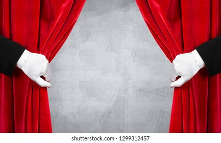 Close up of two hands in white glove open red velvet curtain