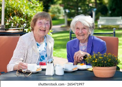 Close up Two Happy Senior Ladies Sitting at the Garden Table with Snacks While Looking at the Camera.