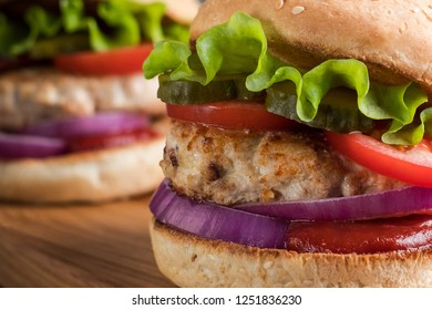 Close up of two homemade turkey burgers with salad, tomatoes, pickles and red onion