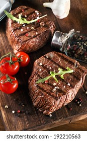 Close up of two juicy thick portions of delicious roasted or grilled beef steak with herbs, peppercorns and spices served on a wooden board with cherry tomatoes in a country kitchen