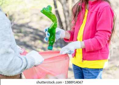 Close up two kids volunteer cleaning plastic pollution in the summer park. Ecology concept